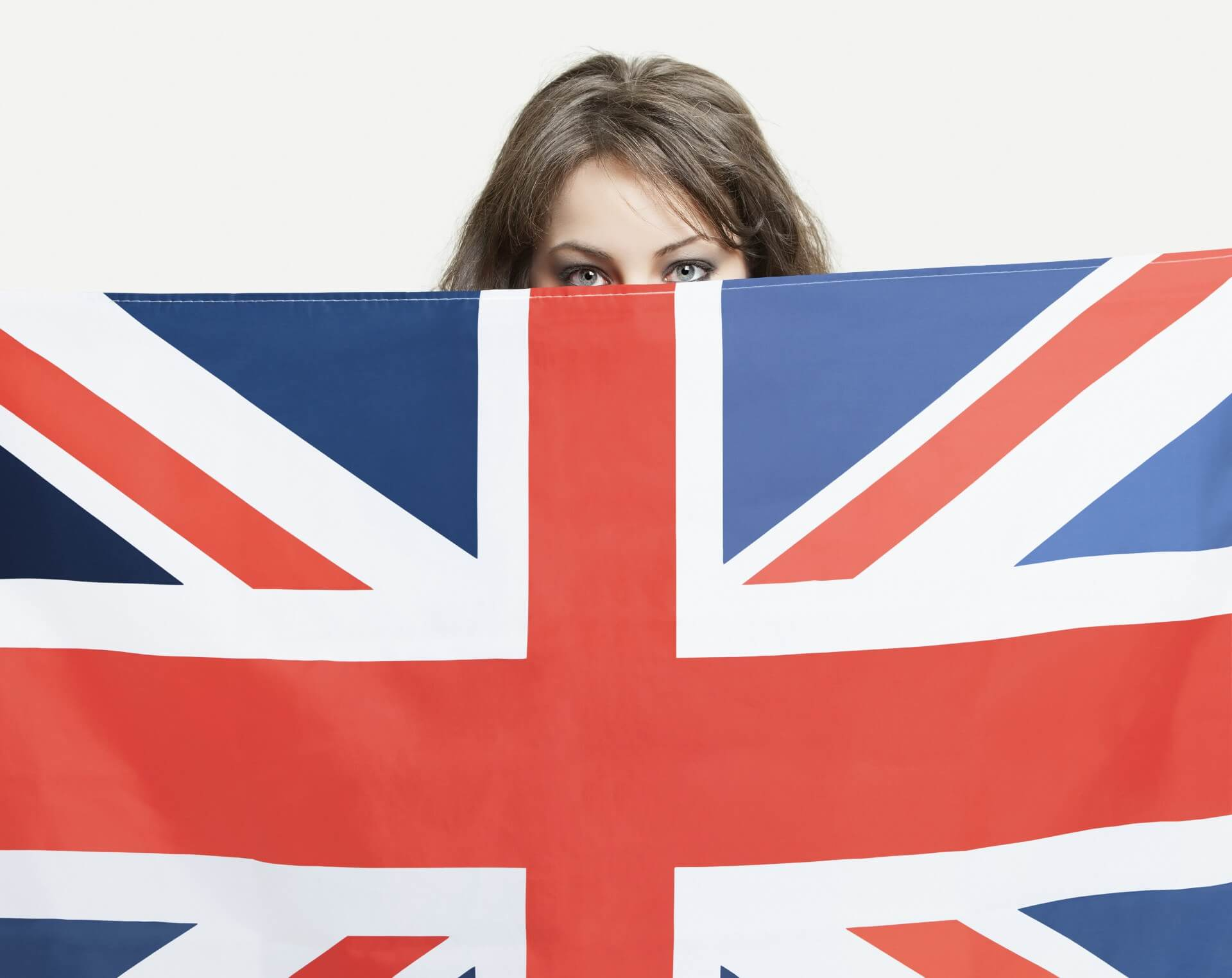 Young woman peeking over British flag against gray background